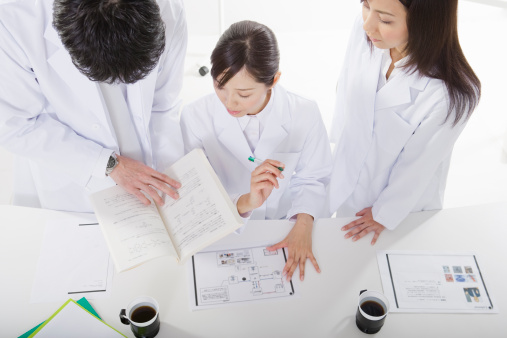 Three scientists working at table, high anlge view